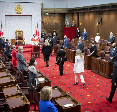 A procession of people are walking along a red carpet towards the front of the room. Three of the individuals are wearing black. One woman is wearing white. There is a throne chair flanked by two Canada flags.