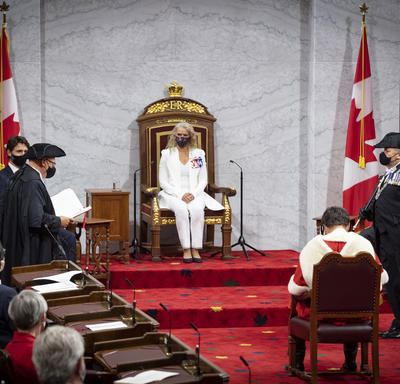 A woman dressed in a white suit is sitting on a throne chair. There are Canada flags on either side of the platform. There is a man sitting in a chair facing her. He is wearing a red and white cape.