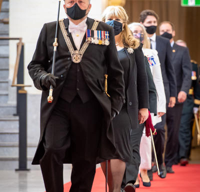 A line of people are walking towards the camera on a red carpet. The man leading the group is wearing a decorated black uniform, carrying a black and gold rod. He is also wearing a black cap and a black face mask.