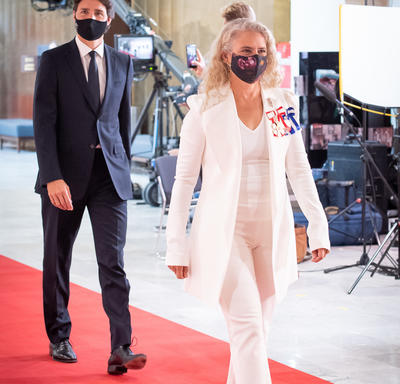 A woman in a white pant suit is walking on a red carpet. She is wearing black heels and a black face mask. A man is walking behind her in a dark suit, also wearing a face mask.