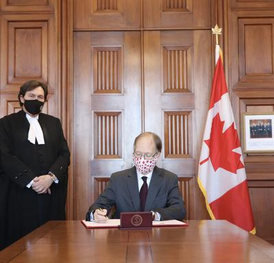 Ian Shugart - clerk of the Privy Council of Canada - sitting at a table. Chief Justice Richard Wagner standing to his right.
