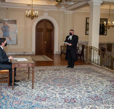 Trois personnes se tiennent debout, éloignées les unes des autres, tandis que l'administrateur est assis à une table.