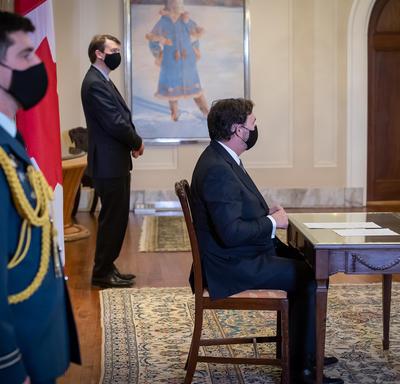 Un aide de camp se tient debout alors que l'administrateur est assis à une table. On distingue le secrétaire à l'arrière-plan.