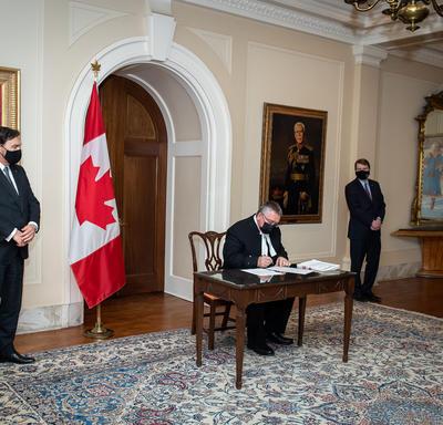 L'administrateur et le secrétaire observent un homme qui signe un document.