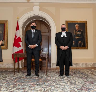 Quatre personnes, dont l'administrateur et le secrétaire, sont debout, tournées vers l'avant. Toutes portent des masques. Un drapeau canadien en arrière-plan.