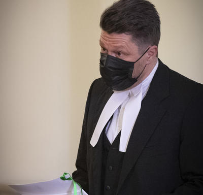 A man, dressed in black with a white collar, reading from a document.