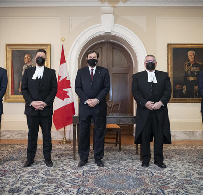 The Administrator, flanked on either side by two people. All wearing masks. One Canadian flag in the background.