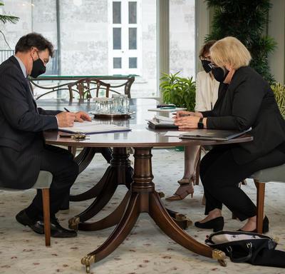 L'administrateur signe un document sur une table en présence de deux femmes.