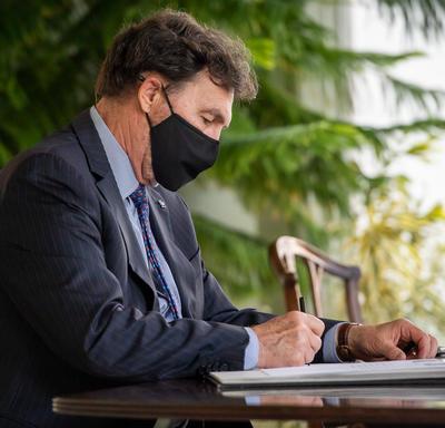 L'administrateur, assis à une table, signe un document.