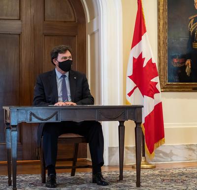 L'administrateur est assis à une table. Le secrétaire se tient à sa gauche. On aperçoit un grand drapeau du Canada derrière et entre les deux hommes.