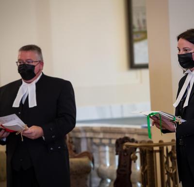 Deux personnes, toutes deux portant une tenue noire avec un col blanc, tiennent des documents.