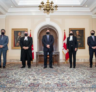 L'administrateur se tient entre quatre personnes. Toutes les personnes portent des masques. Deux drapeaux du Canada se trouvent à l'arrière-plan.