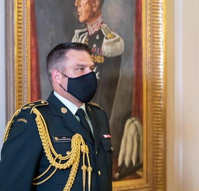 An aide-de-camp standing next to a portrait.