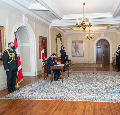 Four people standing at a distance while the Administrator, seated at a table, signs a document.