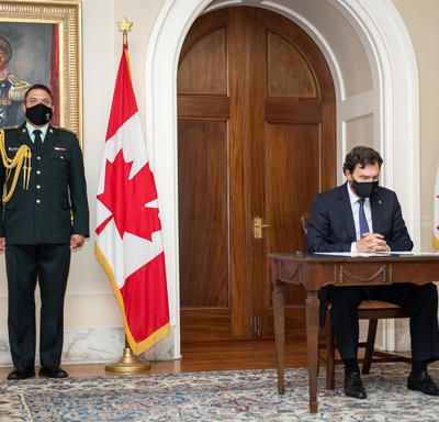 The Administrator sitting at a table. An aide-de-camp is standing to his right.