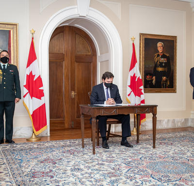 The Administrator sitting at a table. The Secretary is standing to his left while an aide-de-camp stands to his right.