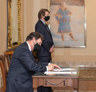 The Administrator sitting at a table signing a document. The Secretary is visible in the background.