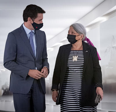 1.Prime Minister Justin Trudeau and Governor General Designate Mary May Simon look at each other as they walk side-by-side down a hall..