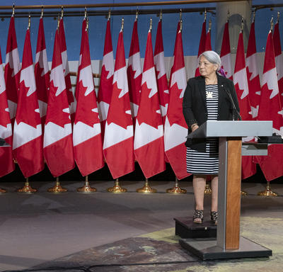 Prime Minister Justin Trudeau and Governor General Designate Mary May Simon each stand at a podium with several Canadian flags behind them.