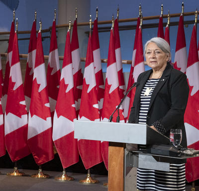 Prime Minister Justin Trudeau and Governor General Designate Mary May Simon each stand at a podium with several Canadian flags behind them. Mary Simon is speaking. Justin Trudeau's head is turned towards her.
