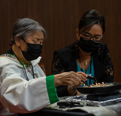 An Inuit Elder lighting the qulliq in the Senate. A woman is seated beside her.
