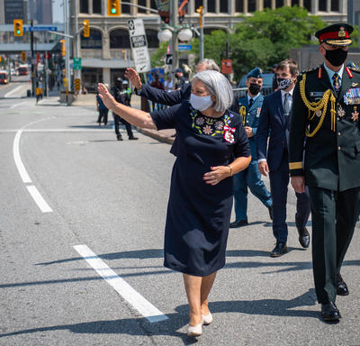 Governor General Mary May Simon waving to the crowd as she walks from the Senate to the National War Memorial.