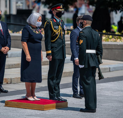Governor General Mary May Simon standing on a small red platform in front of the National War Memorial.