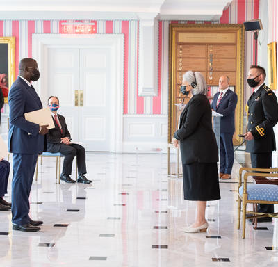 A man in a suit and a face mask hands a document to the Governor General.