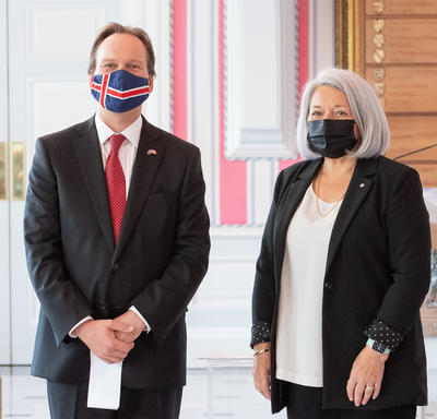 A man in a suit and a face mask stands to right of Governor General Mary May Simon as they pose for a photo.