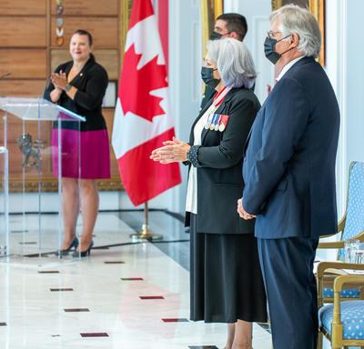 La gouverneure générale Mary May Simon applaudit. Son Excellence Whit Fraser est debout, les mains croisées devant lui. Un drapeau canadien et la maîtresse de cérémonie sont en arrière-plan.