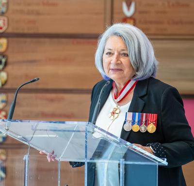 La gouverneure générale Mary May Simon debout derrière le lutrin s'adresse au public.