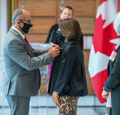Un homme épingle une distinction sur le blouson d'une femme, sous le regard de la gouverneure générale Mary May Simon. Un drapeau canadien décore le fond de la pièce.