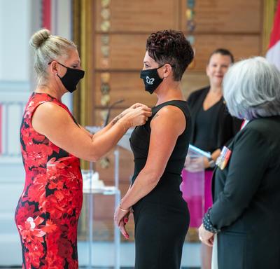 Une femme vêtue d'une robe aux couleurs vives épingle une médaille sur la robe noire d'une autre femme.