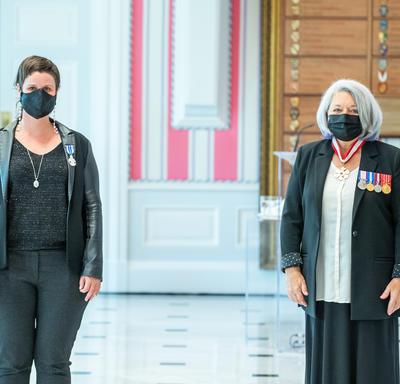 Une femme fraîchement décorée d'une médaille se tient près de la gouverneure générale Mary May Simon. Toutes deux portent un masque.