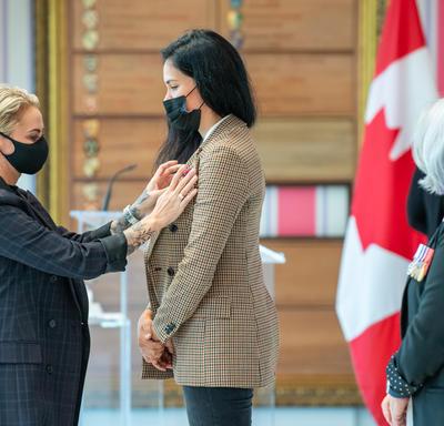 Une femme épingle une médaille sur le blouson d'une autre femme.