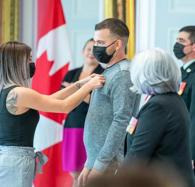 Une femme épingle une médaille sur la chemise d'un homme.