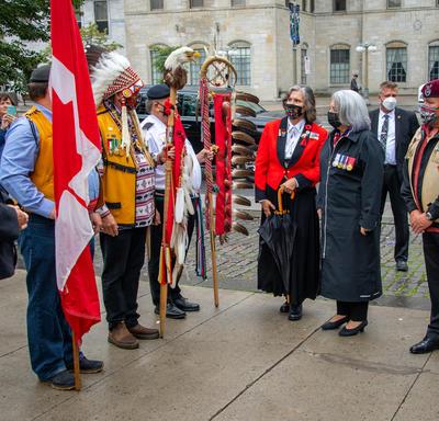 La gouverneure générale échange avec d'autres personnes rassemblées devant le monument.