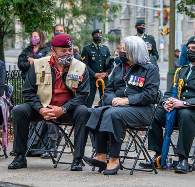 La gouverneure générale est assise avec d'autres personnes pendant la cérémonie en plein air.