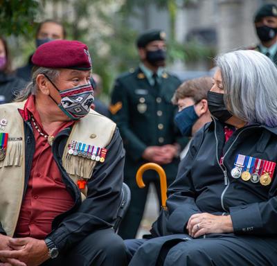 La gouverneure générale discute avec un homme assis à sa droite. Tous deux portent un masque.