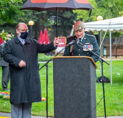Un homme en uniforme parle derrière un lutrin. Un autre homme tient un parapluie pour le protéger de la pluie.