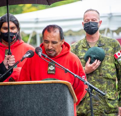 Un homme parle derrière un lutrin. Un militaire se tient derrière lui en tenant son chapeau sur sa poitrine.