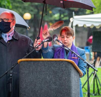 Une femme se tient derrière un lutrin. Un homme tient un parapluie pour la protéger de la pluie.