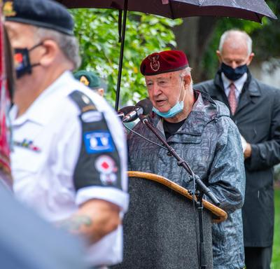 Un ancien combattant parle derrière un lutrin.