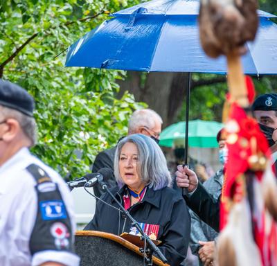 La gouverneure générale prononce son discours. Elle est à l'extérieur. Il pleut.