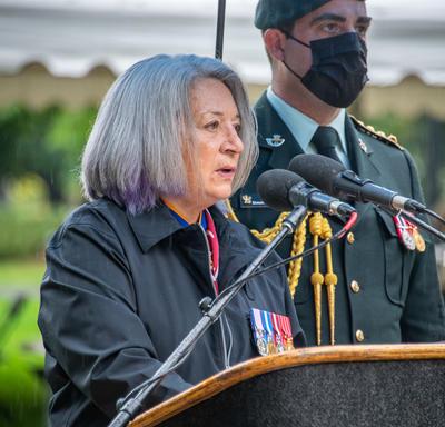 La gouverneure générale prononce son allocution. Un homme en uniforme militaire portant un masque se tient derrière elle. Il pleut.