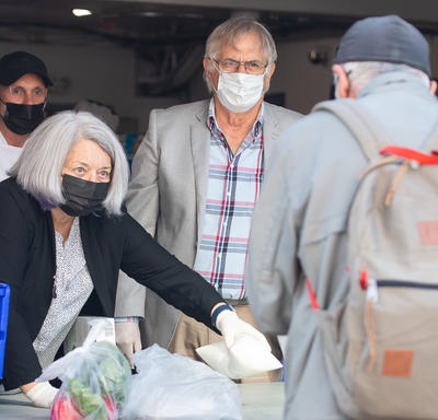 Their Excellencies are serving a meal to a client of the Ottawa Mission. There is a staff member behind them. They are outside and wearing masks.