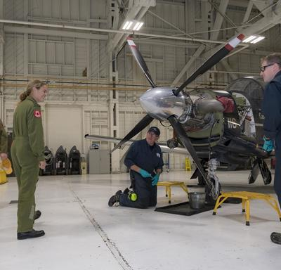 The Governor General interacted with engineers as they were conducting maintenance work on an aircraft.