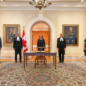 La gouverneure générale est debout, devant une porte ouverte. Une table et une chaise de bois est devant elle. Deux hommes sont à sa gauche. Un homme et une femme sont à sa droite. Tous sont alignés.