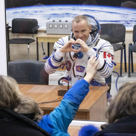 David Saint-Jacques makes a heart shape with his hands as he sits behind the quarantine glass.  He is wearing his astronaut costume.