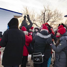 A crowd wearing Canadian tuques and mitts celebrate and look towards the sky.